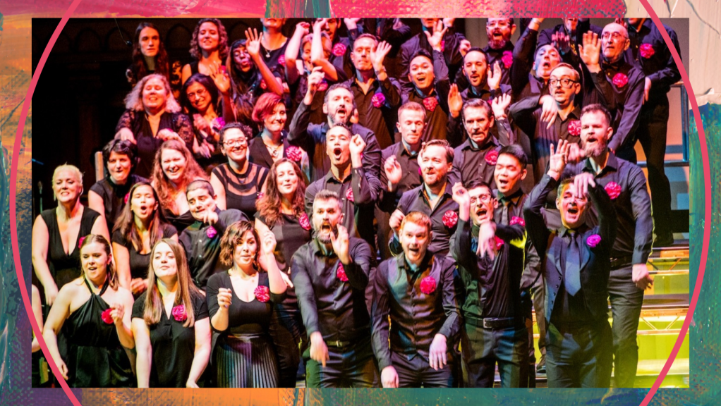 A closer shot of the Pink Singers performing on stage, showing a group of the singers all dressed in black suits and dresses, mid-song and waving their hands in the air.
