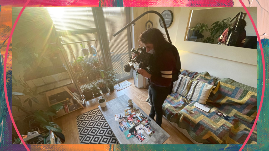 Filming taking place for Polari - a cameraperson is in a small living room, holding a camera and pointing it at an arrangement of photographs laid out on a coffee table.