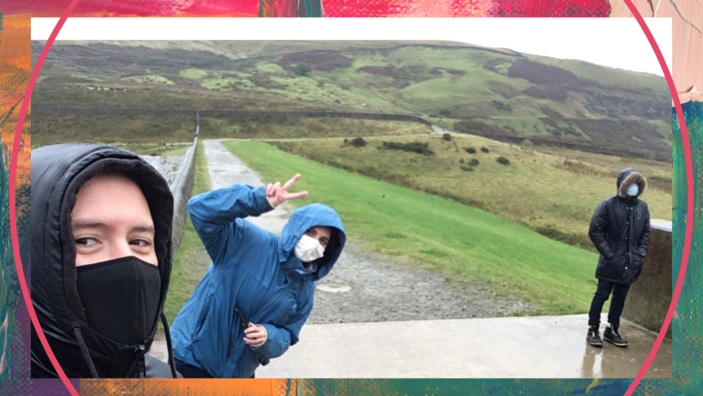 """Filming on location for Polari - three people in masks are seen against a backdrop of rolling hills. They are all wearing waterproof clothing with their hoods up, and masks on. Two of the people are looking at the camera and holding up """"peace"""" finger signs."""